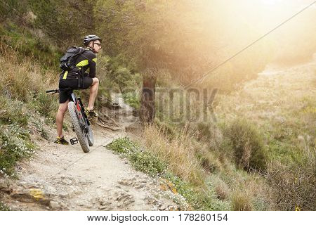 Rear View Of Cyclist Standing On Trail In Forest With His Motor-power E-bike Resting During Workout