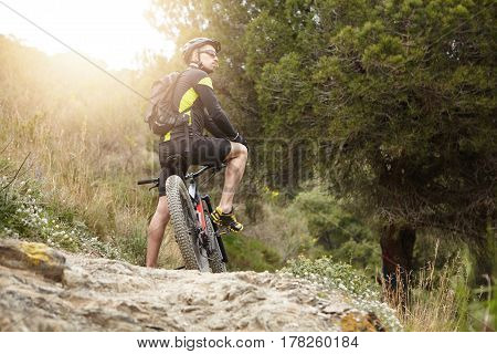 Nature, Travel, Hiking, Cycling And Extreme Sports Concept. Rear Shot Of Young Male Cyclist In Black