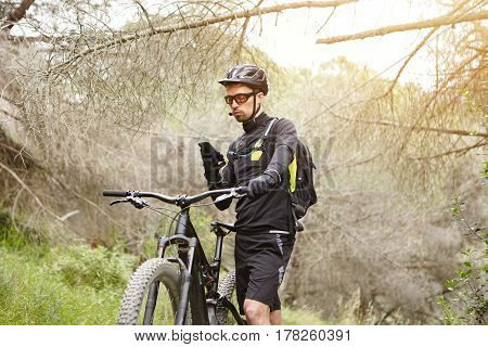 Serious Concentrated Young Cyclist In Black Clothing Studying Map On Smart Phone, Holding Hand On Ha