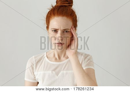 Unhappy Stressed Young Redhead Female With Hair Knot Touching Face While Suffering From Bad Headache