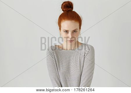 Indoor Shot Of Cute Redhead Girl With Hair Knot Wearing Casual Striped Long-sleeved T-shirt, Her Pos