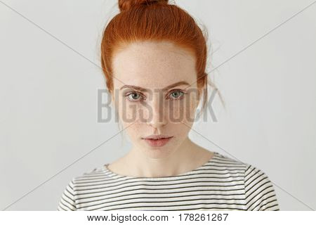 Close Up Shot Of Charming Young Redhead European Woman With Freckles And Hair Bun Looking At Camera