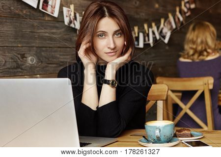 Attractive Young European Female Columnist Dressed Wearing Black Dress Sitting At Cafe Table With Mu