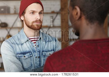 Fashionable Young Bearded Caucasian Man Wearing Trendy Hat And Denim Shirt Smiling While Having Nice