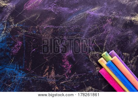 Black Old Empty Chalkboard For Copy Space With Colorful Pieces Of Chalk.