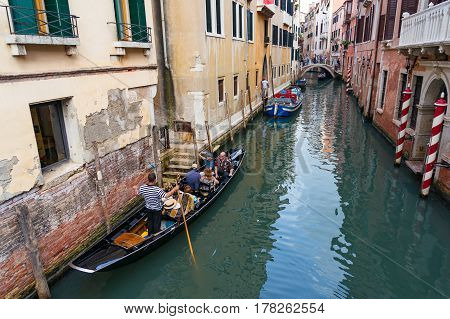Tourists Traveling In Gondola On Venice Channel