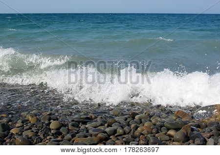 The surf on the shore of the blue sea with shiny wet pebbles on the shore
