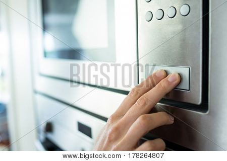 Woman setting up the oven in the kitchen