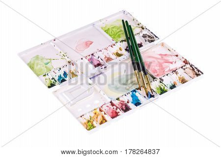 Water Colours Painting Brushes On Multi Colours Paint Tray On White Background. Selective Focus At B