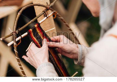 Hands of a woman weaving traditional handmade, thread