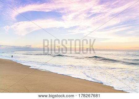 Man fishing and enjoying an amazing sunset in Polihale beach, Kauai island, Hawaii