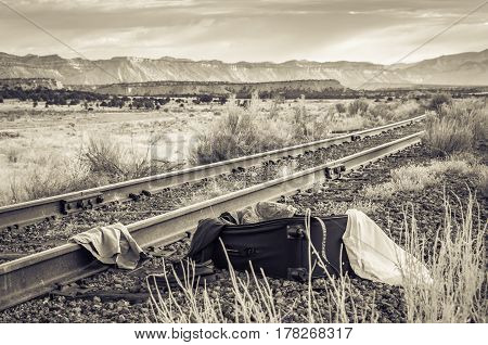 A suitcase by the railroad tracks in black and white
