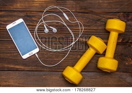 Blank Moblie smart phone with ear phone and dumbbells on wood, healthy life style concept, top view and free space for text
