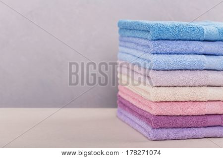 High stack of colorful bath towels on light background. Pastel colors cotton towels. Hygiene fabricspa and textile concept