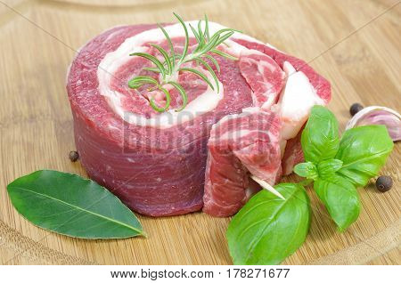 coiled raw beef with basil on cutting board