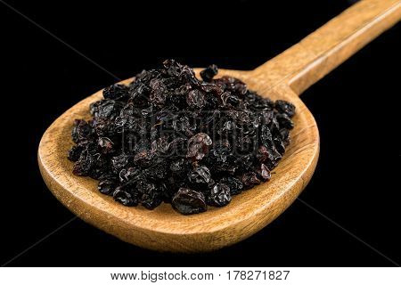 Black raisins in wooden spoon on black background