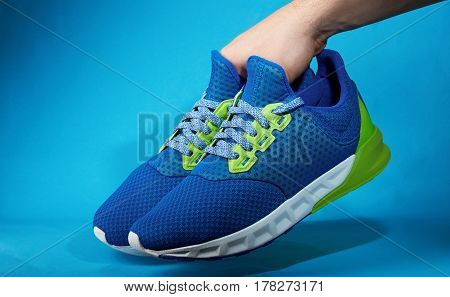 Hand Holding Pair Of New Running Shoes