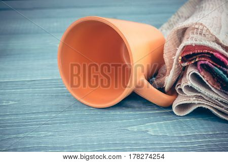 Ceramic cup and plate with an openwork linen napkin on a wooden background. Kitchen Decor in Rustic Style.