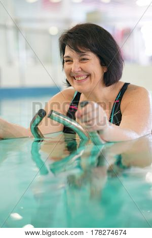 Overweight woman in spa center doing aquabike exercises