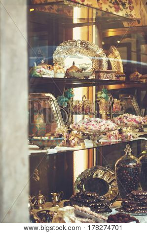 Rich variety of chocolates and candies in display window of italian pastry shop at sunny day at the street of Florence