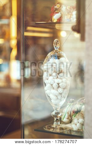 Rich variety of white chocolates candies in glass jars in display window of typical italian pastry shop in the street of Florence with light reflection on window
