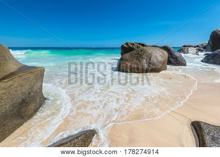 Seascape with large granite boulders and blue summer sky. Carana beach view of Seychelles.