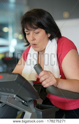 Overweight woman at the gym doing cardio exercises on bike