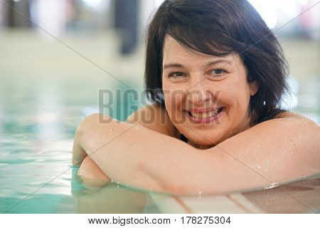Smiling woman in spa center relaxing in swimming-pool