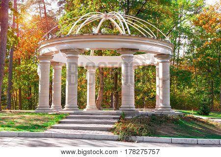 White classic pavilion with columns in autumn park. Sunset light.