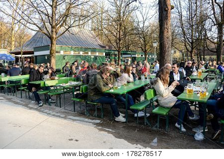 Munich,Germany-March 23,2017:The first patrons enjoy a beer at a beergarden in the Englischer Garten on a sunny spring afternoon
