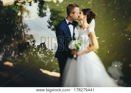 Groom Kisses A Bride Standing On The Lake Shore