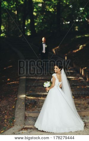 Bride Waits On The Garden Footsteps While Groom Stands On The Background