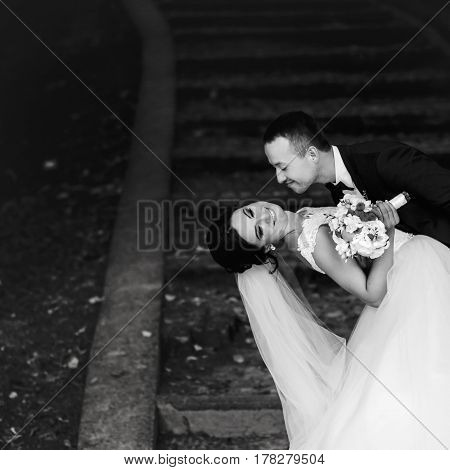 Groom Bends Bride Over Standing On The Park Footsteps Covered With Fallen Leaves