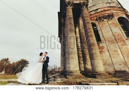 Stunning Wedding Couple Stands In The Cold Weather Behind A Cathedral