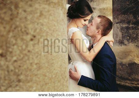 Bride Admires A Groom Standing Between The Pillars