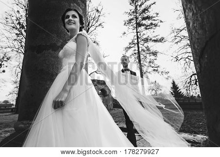 Groom Follows A Bride Among Old Pillars
