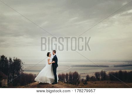 Bride And Groom Stand On The Hill With Great Autumn Landscape Behind Them
