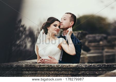 Bride Leans To Groom's Chin Standing With Him On The Old Balcony