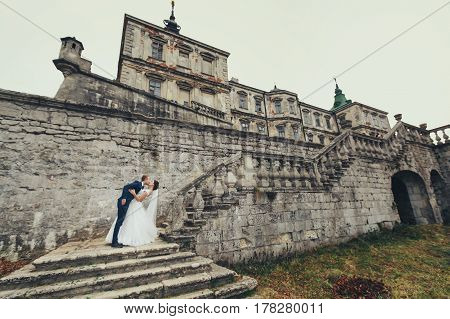 Groom Bends Bride Over Standing On The Stairs To The Old Stone Castle