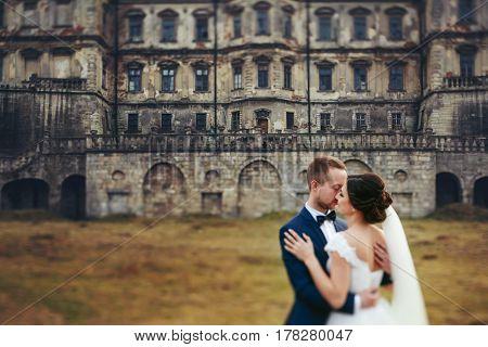 Wedding Couple Hugs Standing On The Bakcyard Of An Old Ruined Castle