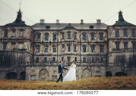 Bride And Groom Walk Along The Yellow Lawn In The Front Of An Old Ruined Castle