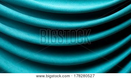 Background of drapery of turquoise fabric close-up