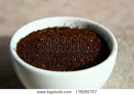 Closeup of grinded coffee beans in a small white cup