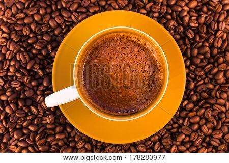 fresh espresso with a beautiful crema and strewn mediumly roasted coffee beans