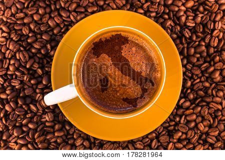 map of Italy on fresh espresso with a beautiful crema and strewn mediumly roasted coffee beans