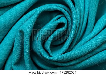 Background of drapery of turquoise fabric close-up. View from above.