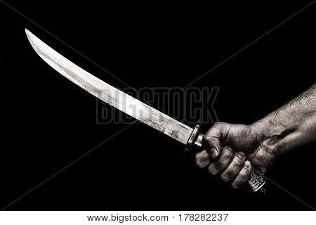 hand holding knife against plank woodknife in hand