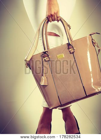 Woman Holding Beige Lacquered Leather Bag.