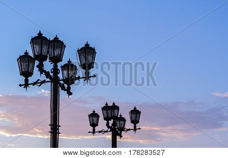 Silhouettes of black wrought iron street lamps against summer sunset sky.