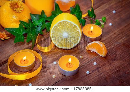 Citrus and herbs aroma concept. Burning yellow aroma candles, tangerine, lemon and ivy branch with green leaves, decorated by yellow satin ribbon, on a wooden background